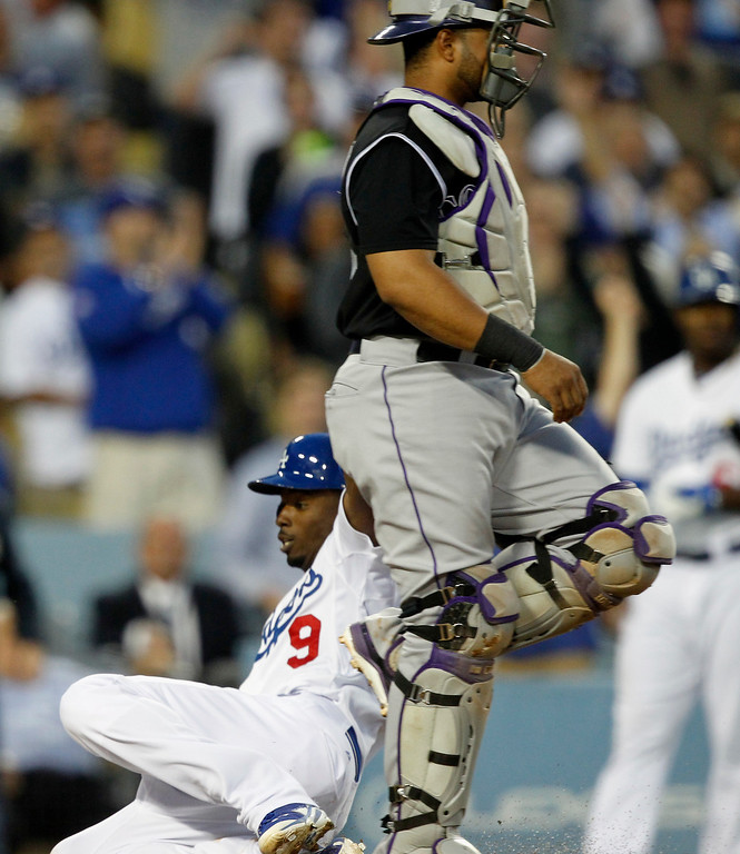 . Los Angeles Dodgersí Dee Gordon (9) scores on a triple, and an error by Colorado Rockies left fielder Charlie Blackmon, without a throw to Rockies catcher Wilin Rosario, right, in the third inning of a baseball game on Monday, June 16, 2014, in Los Angeles.   (AP Photo/Alex Gallardo)