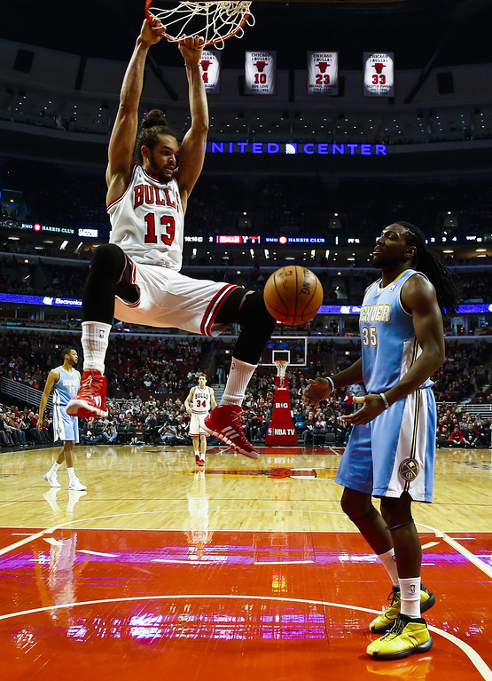 . Chicago Bulls center Joakim Noah (L) swings from the basket after dunking the ball in front of Denver Nuggets forward Kenneth Faried (R) in the first half of their NBA game at the United Center in Chicago, Illinois, USA, 21 February 2014  EPA/TANNEN MAURY