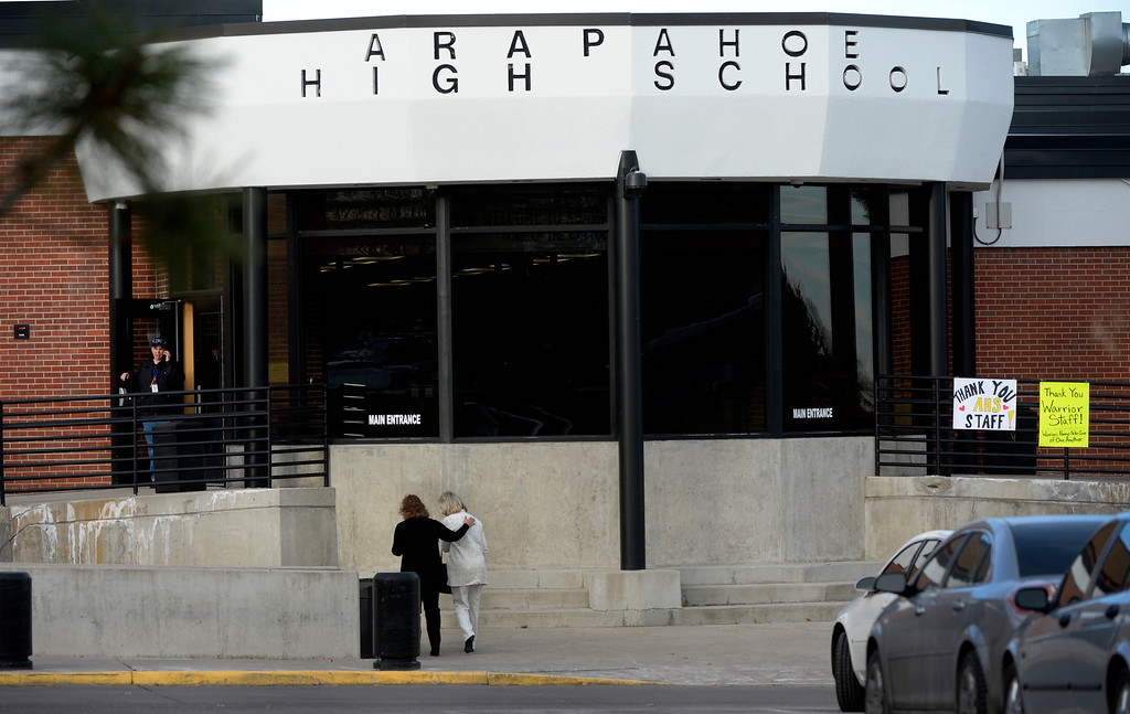 . Two women approach the entrance to Arapahoe High School in Centennial, CO December 18, 2013. Faculty and staff were allowed to return to the school to retrieve belongings left in the building. (Photo By Craig F. Walker / The Denver Post)