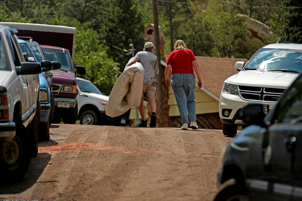 . Manitou Springs, CO. - July 02: Mark Marinen carries a salvaged mattress form the home of a friend after a flash flood washed through houses, streets and businesses when a downpour hit over the Waldo Canyon burn scar in El Paso County July 02, 2013 Manitou Springs, Colorado. (Photo By Joe Amon/The Denver Post)