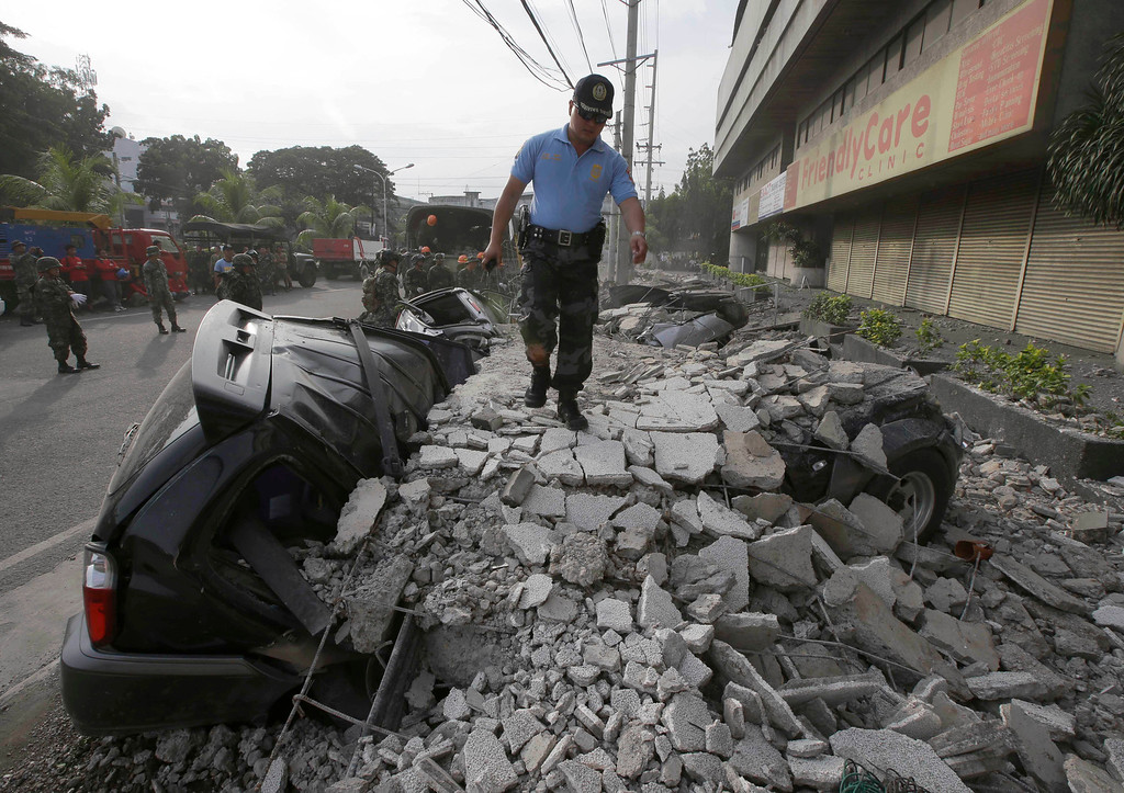 . A police officer surveys the damage following a 7.2-magnitude earthquake that hit Cebu city in central Philippines Tuesday, Oct. 15, 2013.  (AP Photo/Bullit Marquez)