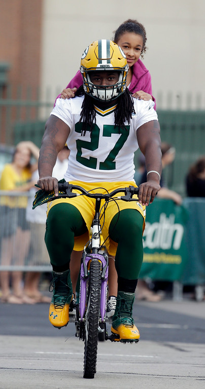 . Green Bay Packersí Eddie Lacy rides a bike to NFL football training camp on Saturday, July 26, 2014, in Green Bay, Wis. (AP Photo/Morry Gash)