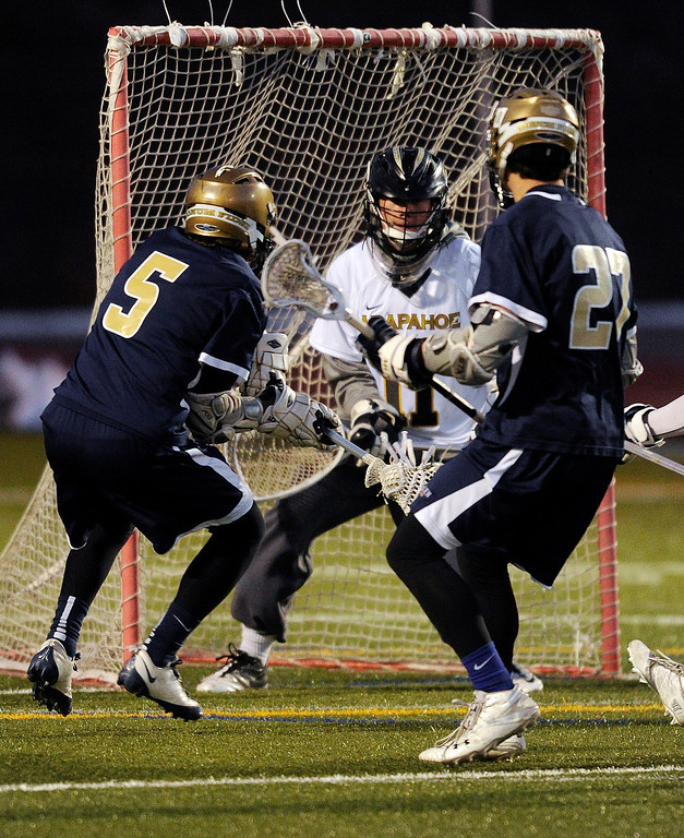 . LITTLETON, CO. - APRIL 10: Mullen senior middie Austin Smith (5) gave the Mustangs a lead in the second quarter with a goal past Warriors goalie Ryan Smith (11). The Mullen High School boy\'s lacrosse team defeated Arapahoe 8-7 Wednesday night, April 10, 2013. Photo By Karl Gehring/The Denver Post)