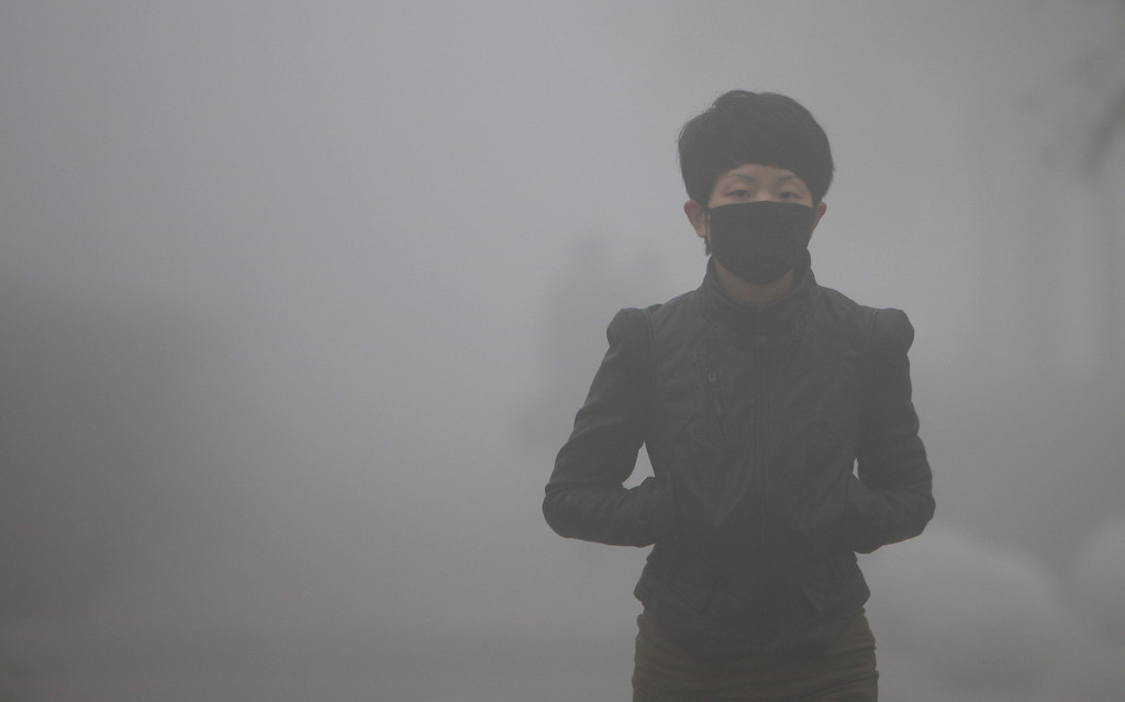 . A woman wearing mask walks along a road as heavy smog engulfs the city on October 21, 2013 in Changchun, China. Expressways, schools and an airport remain closed as heavy smog continues to disrupt northeast China.  (Photo by ChinaFotoPress/Getty Images)