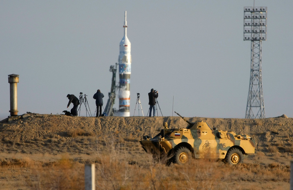 . A police APC drives past cameramen preparing to film launch of  the Soyuz-FG rocket booster with the Soyuz TMA-11M spaceship carrying a new crew to the International Space Station, at the Russian leased Baikonur cosmodrome, Kazakhstan, Thursday, Nov. 7, 2013. The Russian rocket carries Japanese astronaut Koichi Wakata, Russian cosmonaut Mikhail Tyurin and US astronaut Rick Mastracchio. The crew will deliver Olympic torch to space as part of the ongoing Olympic torch relay. The torch will be brought back along with the station\'s current crew. (AP Photo/Dmitry Lovetsky)