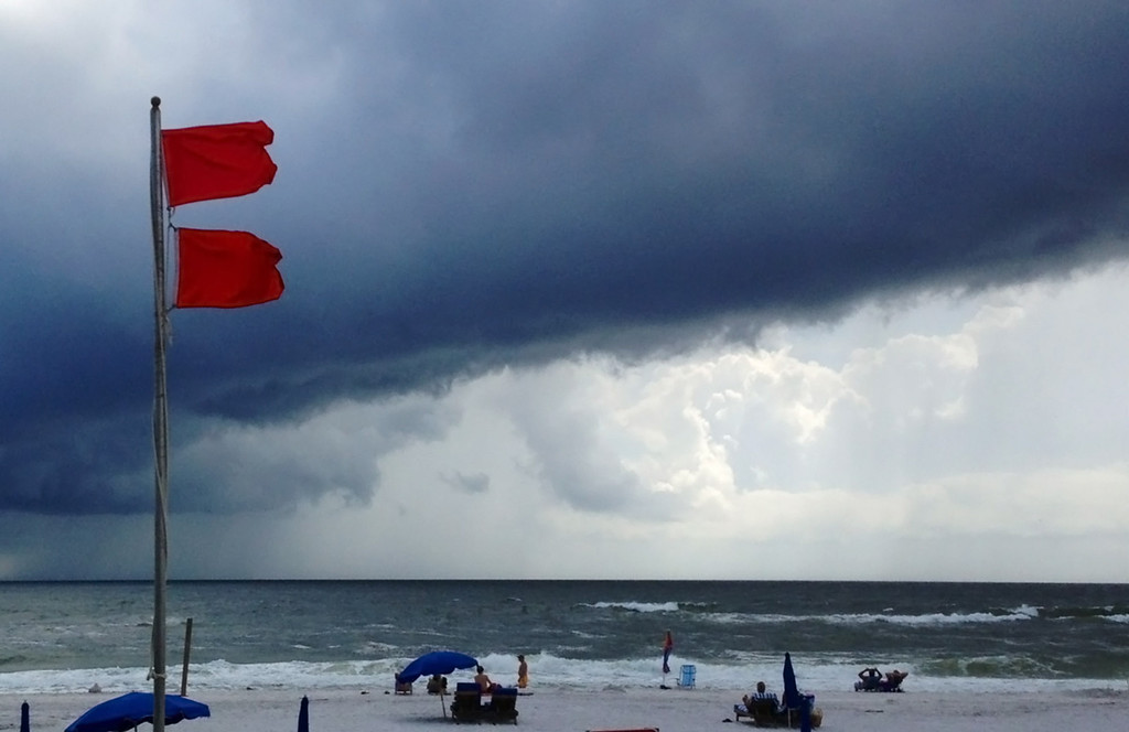 . Red flags warn swimmers to stay out of the Gulf of Mexico as a squall from Tropical Storm Karen moves offshore at Gulf Shores, Ala., on Saturday, Oct. 5, 2013. The beaches remained open, but authorities said dangerous underwater rip currents made the waters too dangerous to enter. (AP Photo/Jay Reeves)