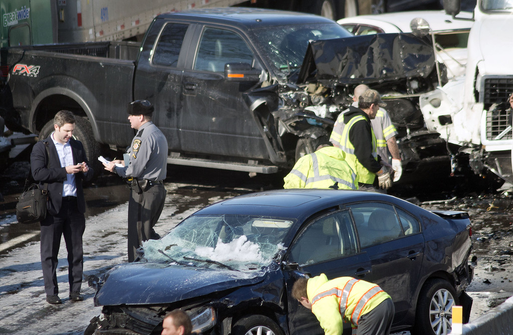 . A Pennsylvania state police officer takes a statement from a victim of the crash on the scene of a 100 car chain reaction pileup accident on the Pennsylvania Turnpike eastbound February 14, 2014 in Feasterville, Pennsylvania. (Photo by William Thomas Cain/Getty Images)