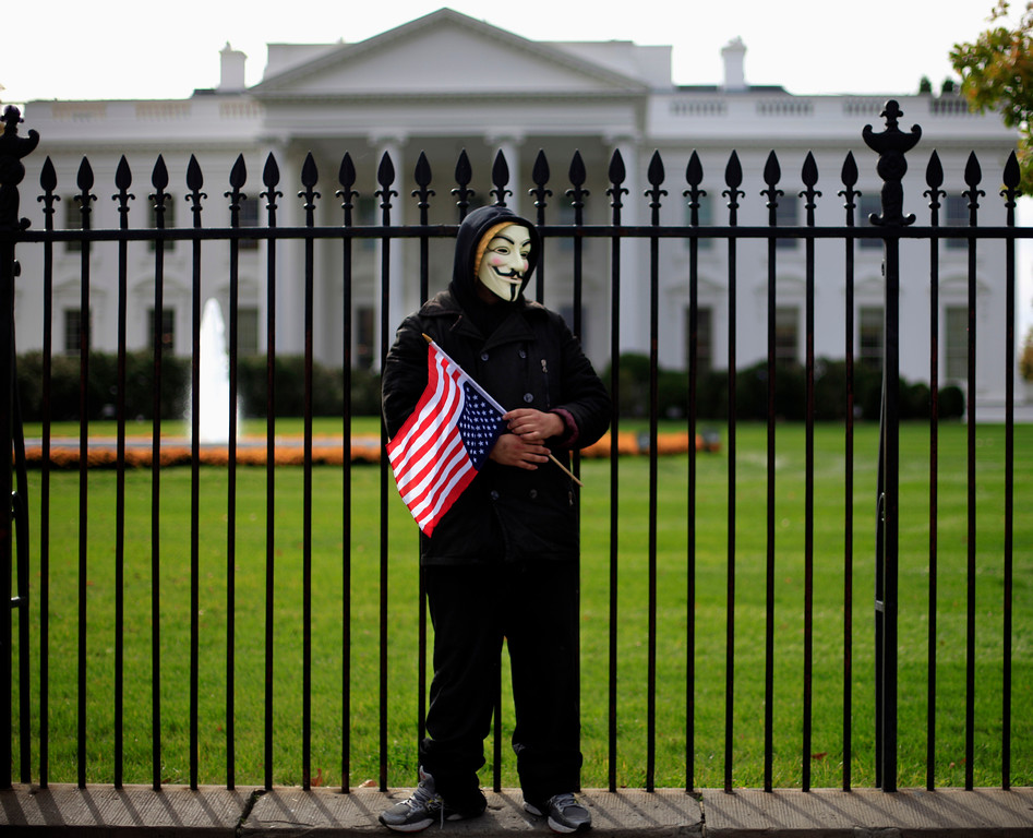 ". A demonstrator stands along the fence during a protest in front of the White House in Washington, Tuesday, Nov. 5, 2013, against corrupt governments and corporations, part of a Million Mask March of similar rallies around the world on Guy Fawkes Day. Guy Fawkes Day, Nov. 5,  is to mark when English authorities arrested Guy Fawkes, the leader of the ""Gunpowder Plot\"" during a to blow up Houses of Parliament in 1605.   (AP Photo/Pablo Martinez Monsivais)"