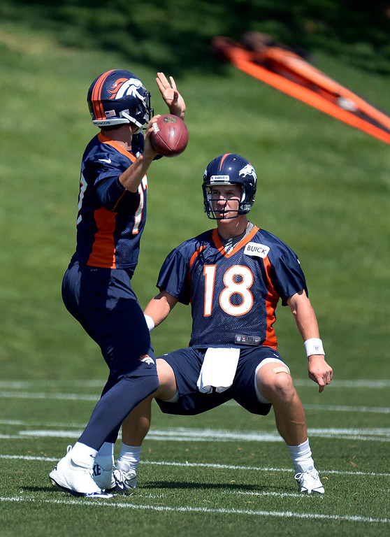. Peyton Manning (18) of the Denver Broncos tries to distract Brock Osweiler (17) during his throw at mini camp June 11, 2013 at Dove Valley. (Photo By John Leyba/The Denver Post)