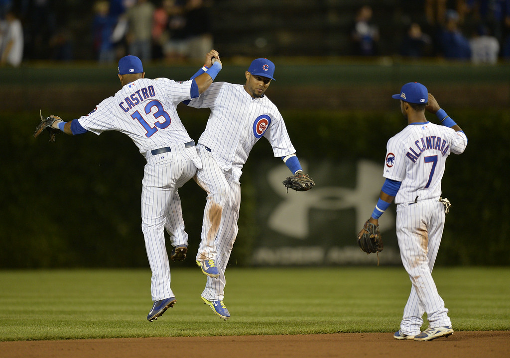 . Starlin Castro #13, Emilio Bonifacio #64 and Arismendy Alcantara #7 of the Chicago Cubs celebrate a win over the Colorado Rockies on July 28, 2014 at Wrigley Field in Chicago, Illinois. The Cubs defeated the Rockies 4-1.  (Photo by Brian Kersey/Getty Images)
