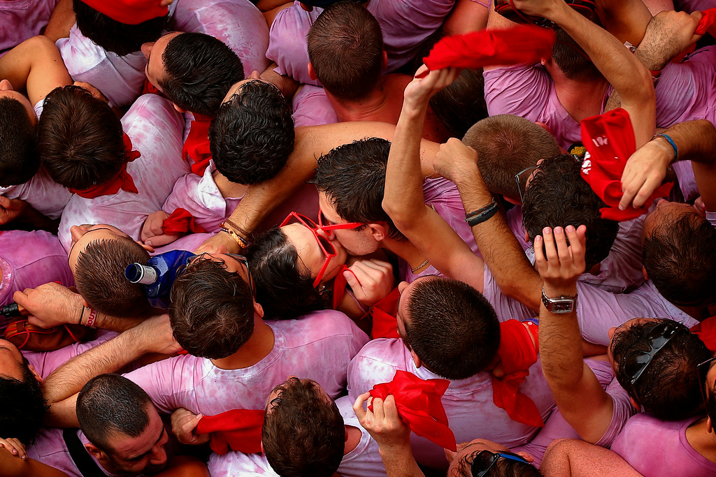 ". A couple of revelers kiss during the launch of the \'Chupinazo\' rocket, to celebrate the official opening of the 2014 San Fermin fiestas, in Pamplona, Spain, Sunday, July 6, 2014. Revelers from around the world kick off the festival with a messy party in the Pamplona town square, one day before the first of eight days of the running of the bulls glorified by Ernest Hemingway\'s 1926 novel ""The Sun Also Rises.\"" (AP Photo/Daniel Ochoa de Olza)"