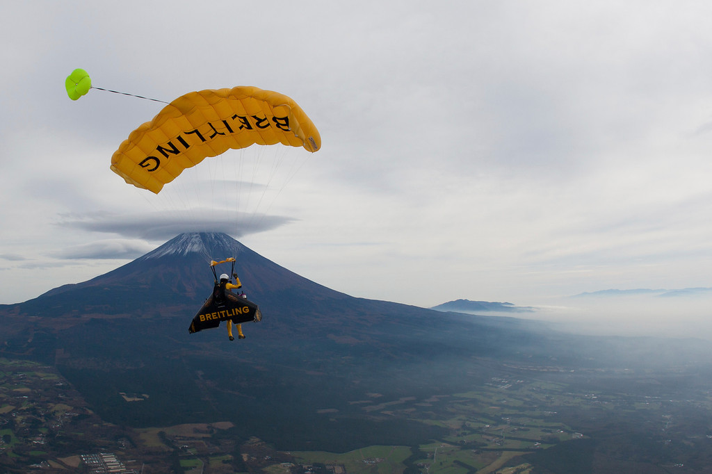 . In this photo taken Sunday, Nov. 3, 2013 and provided by Breitling, Yves Rossy, known as the Jetman, descends by parachute after flying around Mount Fuji in Japan. T(AP Photo/Bruno Brokken, Breitling)