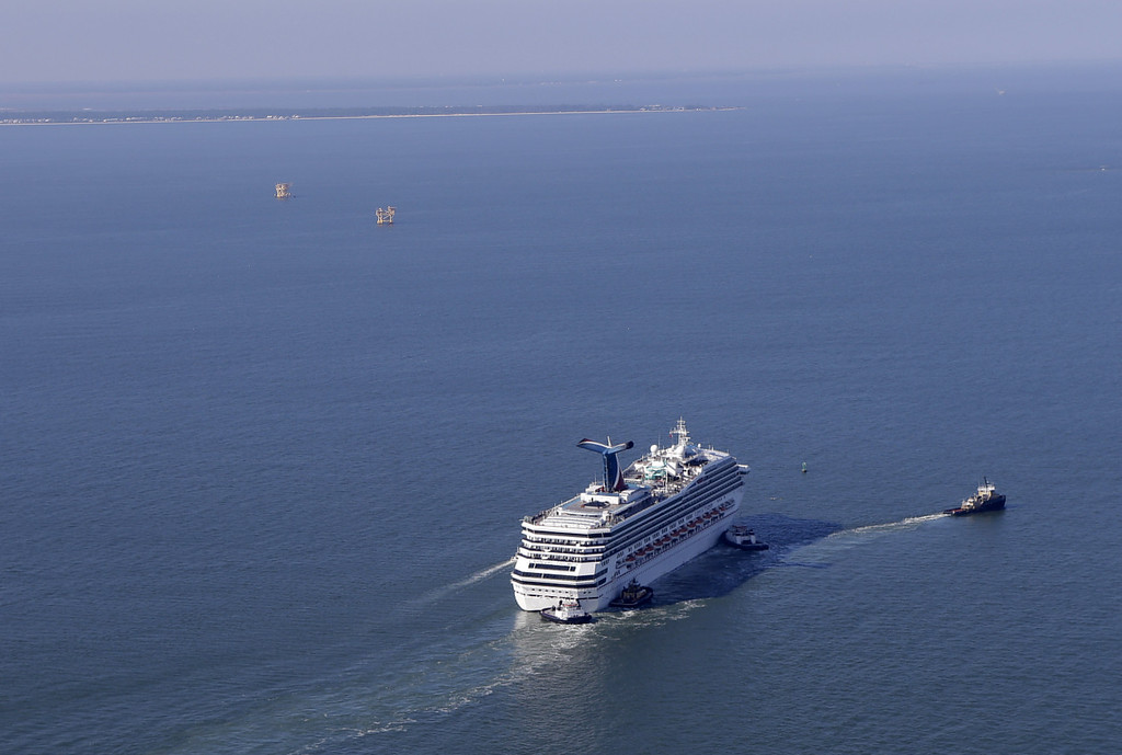 . A disabled Carnival Lines cruise ship is towed to harbor off Mobile Bay, Ala., Thursday, Feb. 14, 2013.   (AP Photo/Gerald Herbert)