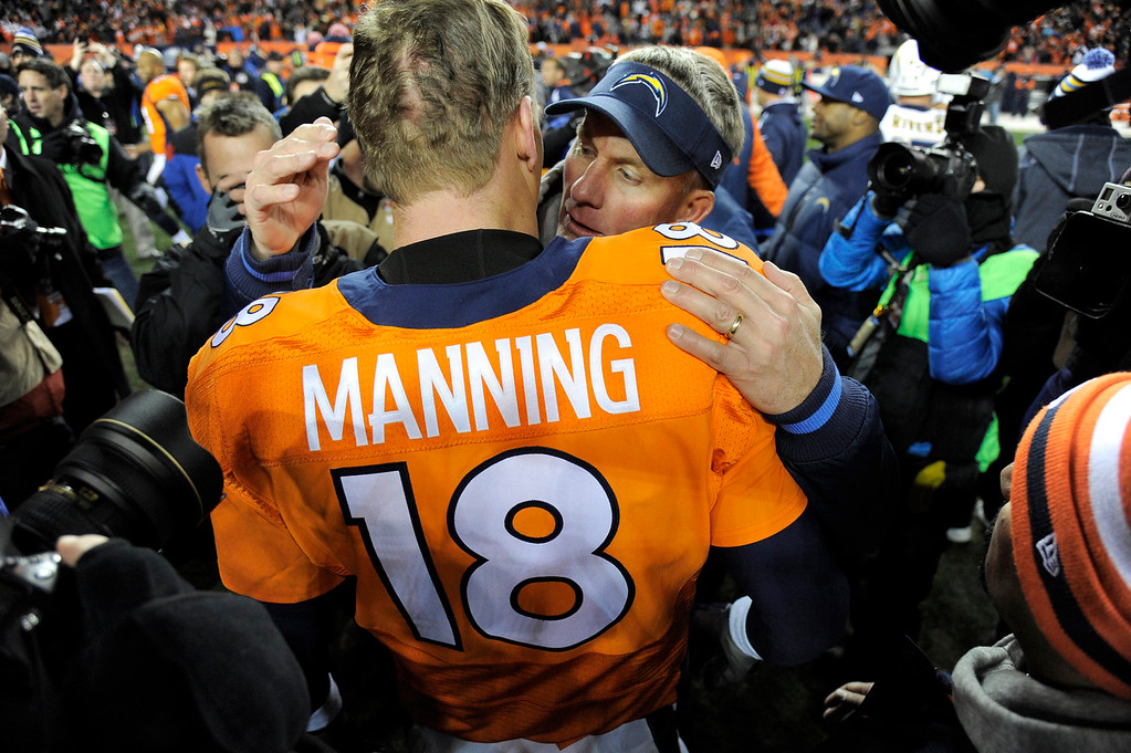 . Denver Broncos quarterback Peyton Manning (18) gets a hug from San Diego Chargers head coach Mike McCoy after the Denver Broncos beat the San Diego Chargers 24 - 17. The Denver Broncos vs. The San Diego Chargers in an AFC Divisional Playoff game at Sports Authority Field at Mile High in Denver on January 12, 2014. (Photo by John Leyba/The Denver Post)