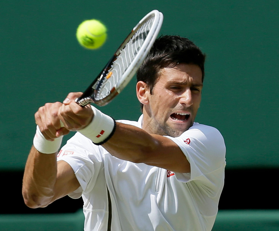 . Novak Djokovic of Serbia returns to Andy Murray of Britain during the Men\'s singles final match at the All England Lawn Tennis Championships in Wimbledon, London, Sunday, July 7, 2013. (AP Photo/Alastair Grant)