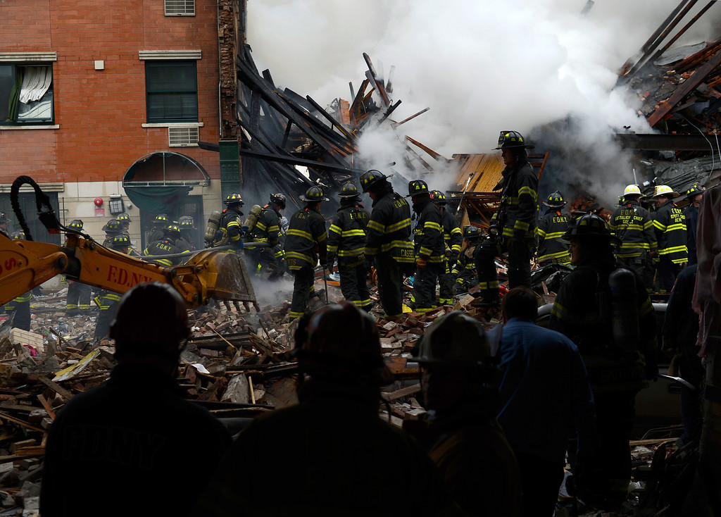. In this image handout provided by the Office of Mayor of New York, firefighters from the Fire Department of New York (FDNY) walk in the rubble as they respond to a five-alarm fire and building collapse at 1646 Park Ave in the Harlem neighborhood of Manhattan March 12, 2014 in New York City.  (Photo by Rob Bennett/Office of Mayor of New York/Getty Images)