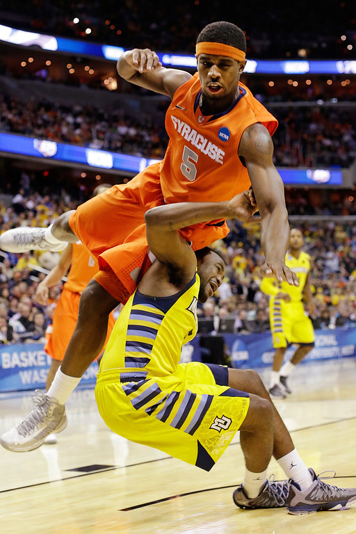 . Syracuse forward C.J. Fair (5) falls on Marquette guard Junior Cadougan (5) during the first half of the East Regional final in the NCAA men\'s college basketball tournament, Saturday, March 30, 2013, in Washington. (AP Photo/Pablo Martinez Monsivais)