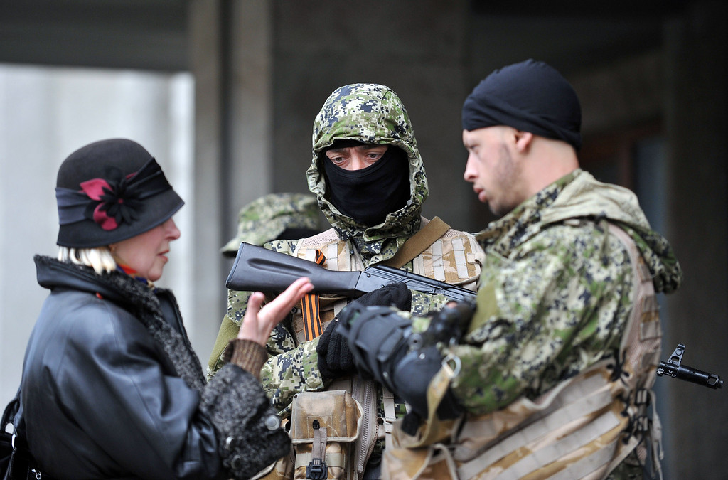 . A woman speaks to armed men in military fatigues standing guard outside a regional administration building they seized in the eastern Ukrainian city of Slavyansk on April 14, 2014. AFP PHOTO / GENYA SAVILOV/AFP/Getty Images