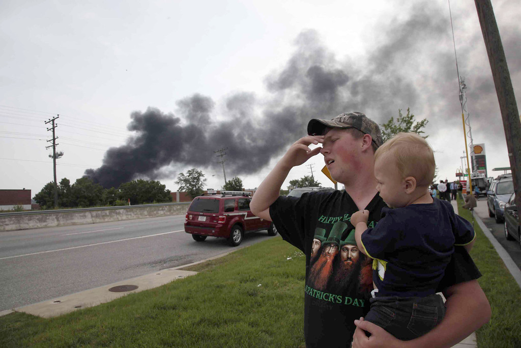 . Mark Paugh carries his 15-month-old son Ryan as they watch smoke from a train derailment in White Marsh, Md., Tuesday, May 28, 2013, in Rosedale, Md. (AP Photo/Charles Dharapak)
