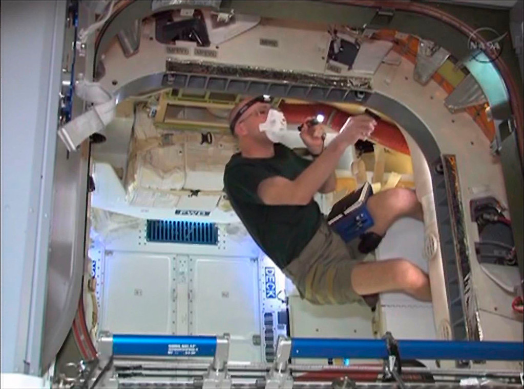 . International Space Station flight engineer Don Pettit inspects the seal around the hatch of the new SpaceX Dragon commercial cargo craft after the opening of the new module in this image from NASA TV May 26, 2012.    REUTERS/NASA TV