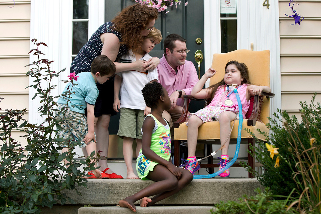 . Lung transplant recipient Sarah Murnaghan, right, accompanied by her sister Ella, 8, center, brothers Finn, 5, left, and Sean, 7, father Fran, and mother Janet, waves during a news conference after arriving home from the hospital Tuesday, Aug. 27, 2013, in Newtown Square, Pa.  Sarah Murnaghan, who has end-stage cystic fibrosis, received two lung transplants this summer at the Children\'s Hospital of Philadelphia after a federal judge intervened in her parents\' lawsuit challenging national transplant rules that put her at the end of the waiting list for adult lungs. (AP Photo/Matt Rourke)