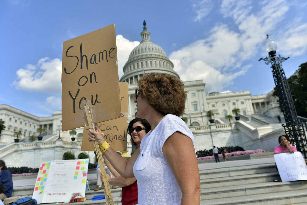 ". Protesters display placards during a demonstration in front of the US Capitol in Washington, DC, on October 1, 2013 urging congress to pass the budget bill. US President Obama slammed Republicans for shutting down the government as part of an ""ideological crusade\"" designed to kill his signature health care law.  AFP Photo/Jewel SAMAD/AFP/Getty Images"