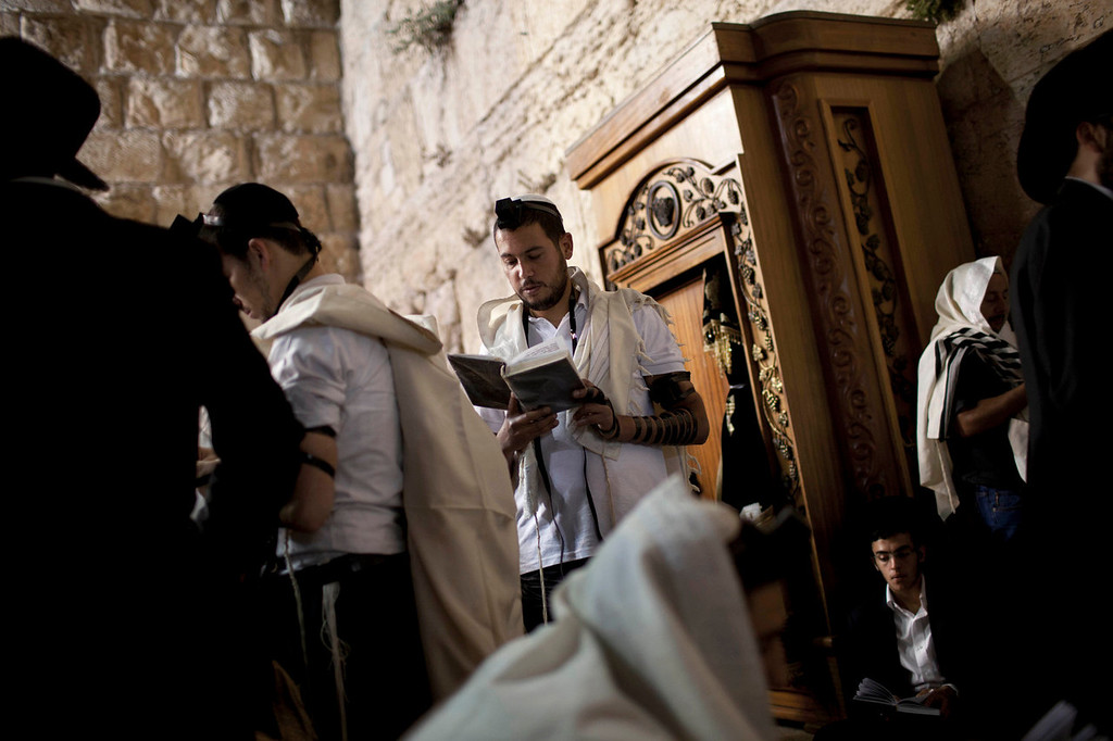 . Israeli Orthodox Jew Shahar Hadar, prays during the mourning ritual of Tisha B\'Av at the Western Wall, the holiest site where Jews can pray in Jerusalem\'s old city on Tuesday, July 16, 2013. Hadar, a telemarketer by day, has taken the gay Orthodox struggle from the synagogue to the stage, beginning to perform as one of Israel\'s few religious drag queens. His drag persona is that of a rebbetzin, a female rabbinic advisor, a wholesome guise that stands out among the sarcastic and raunchy cast of characters on Israel\'s drag queen circuit.  (AP Photo/Oded Balilty)