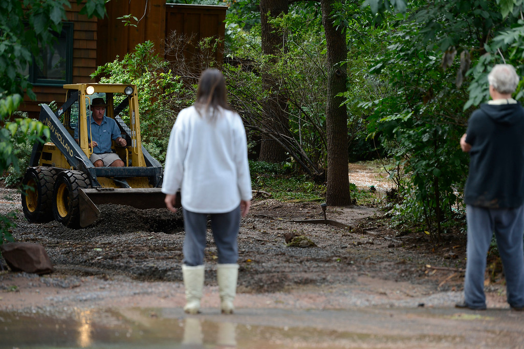 . BOULDER, CO - SEPTEMBER 13: Matt Corley, drives a �skid loader� to level out a flooded out driveway for Boulder Colorado residents, Joyce, left, and Geoffrey Pollich along Juniper Ave. Friday afternoon, September 13, 2013. (Photo By Andy Cross/The Denver Post)