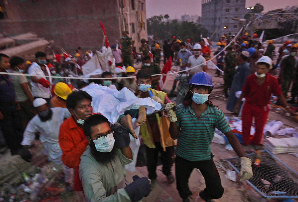. The body of a Bangladeshi garment worker is carried by rescue workers after being removed from the rubble of a building that collapsed Wednesday in Savar, near Dhaka, Bangladesh, Saturday, April 27, 2013. Police in Bangladesh arrested two owners of a garment factory in a shoddily-constructed building that collapsed this week, killing at least 324 people, as protests spread to a second city Saturday with hundreds of people throwing stones and setting fire to vehicles. (AP Photo/Kevin Frayer)