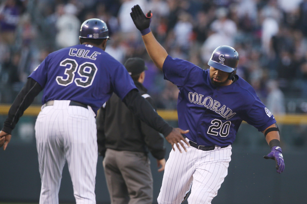 . Colorado Rockies third base coach Stu Cole, left, congratulates Wilin Rosario as he circles the bases after hitting a three-run home run against the San Francisco Giants in the first inning of a baseball game in Denver on Monday, April 21, 2014. (AP Photo/David Zalubowski)