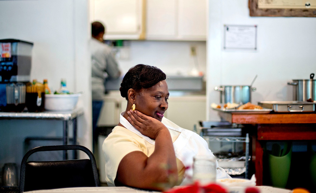 . Lula Walker, 65, owner of Lula\'s Kitchen, rests after serving lunch to a tour group as her granddaughter Stephanie Grovner, 21, helps in the kitchen in the only restaurant in the Hog Hammock community of Sapelo Island, Ga. on Wednesday, May 15, 2013. Walker is one of roughly 47 residents, most of them descendants of West African slaves known as Geechee, who remain on Sapelo Island, the coastal Georgia island where their ancestors were brought to work a plantation in the early 1800s. Once freed, the former slaves were able to acquire land and created settlements on the island, of which only the tiny 464-acre Hog Hammock community still exists. (AP Photo/David Goldman)