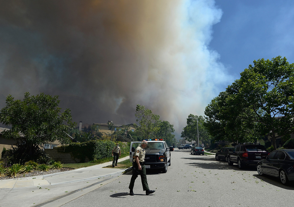 . Ventura County Fire Sheriffs go door to door asking residents if they need any assistance as a wildfire approaches homes on May 2, 2013 in Newbury Park, California.  (Photo by Kevork Djansezian/Getty Images)