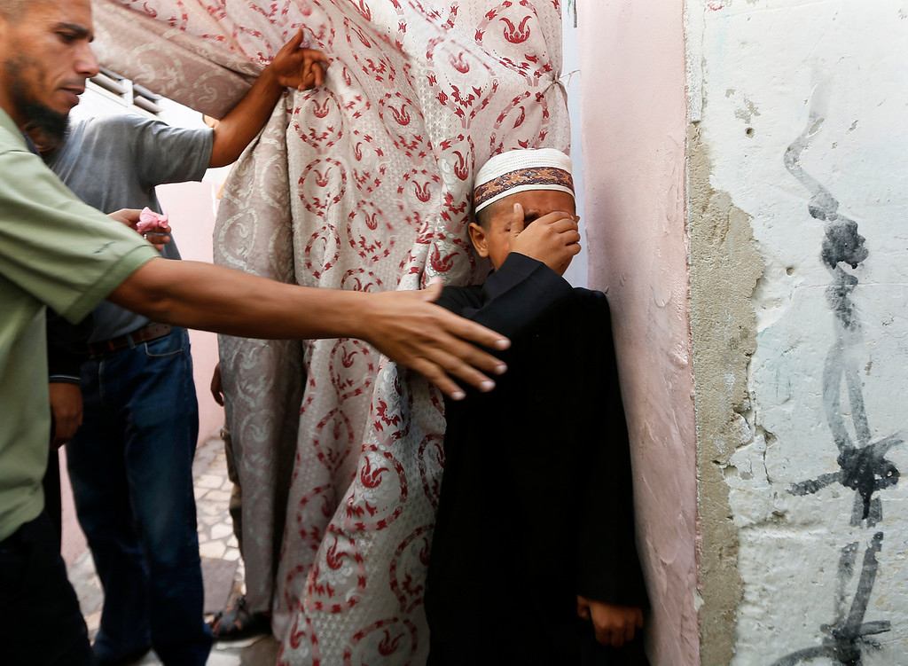 . The son of Salafi Islamist Hisham al-Saedni mourns during his father\'s funeral in Bureij refugee camp in the central Gaza Strip October 14, 2012. Two Gaza militants killed by Israel on Saturday, one of them al-Saedni, were the most senior al Qaeda affiliates in the Palestinian enclave, with links to jihadi networks in Egypt, Jordan and Iraq, sources said on Sunday. REUTERS/Mohammed Salem
