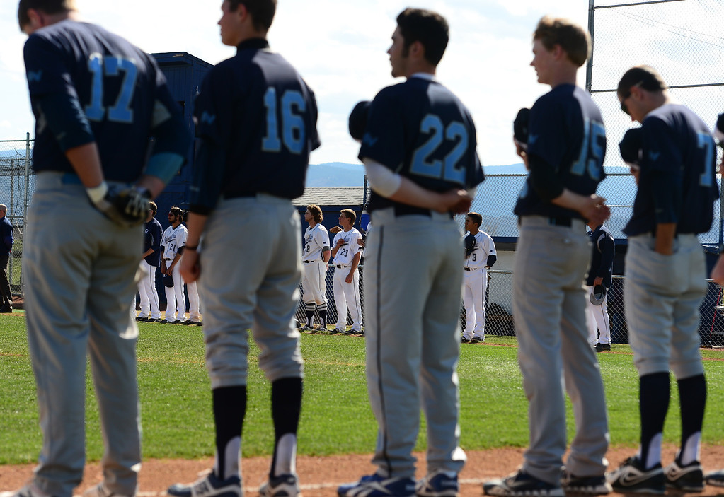 . LITTLETON, CO - APRIL 16,  2014: The Columbine Rebels in white and the Ralston Valley Mustangs in blue hold their hats and hand to their hearts during the sining of the national anthem before their game at Columbine High School in Littleton, Co on April 17, 2014. Columbine pitcher Blake Weiman had a great game and was taken out in the fifth inning when the Rebels were up 8 to 1 over the Mustangs. (Photo By Helen H. Richardson/ The Denver Post)