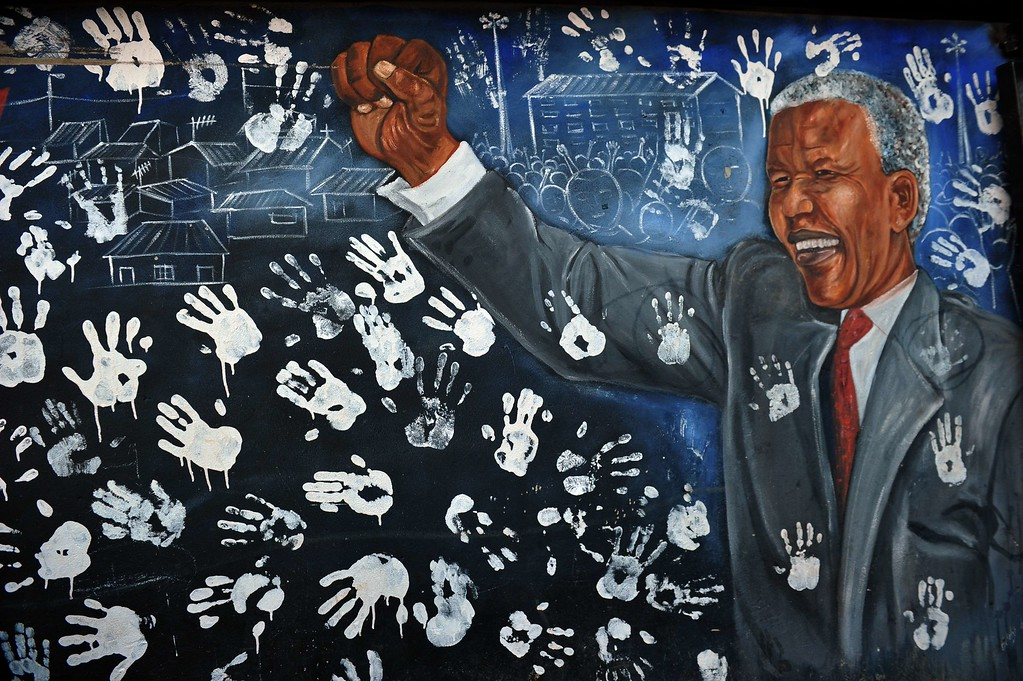 ". A mural showing former South African President Nelson Mandela is pictured near his former house in Alexandra township on June 28, 2013. US President Barack Obama arrived in South Africa on Friday to pay homage to his hero Nelson Mandela, who was said to be showing ""great improvement\"" in hospital. ALEXANDER JOE/AFP/Getty Images"