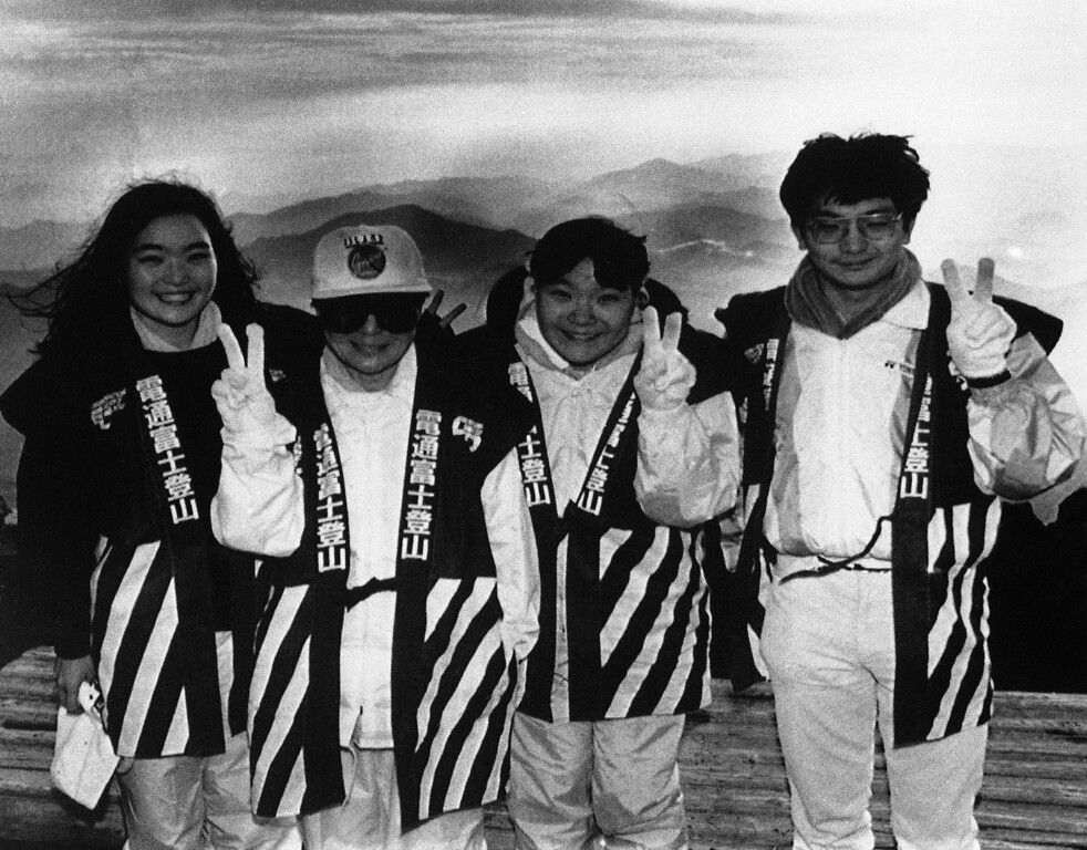 ". Yoko Ono, second from left, widow of John Lennon, signals her hopes for world peace in celebration of ""Harmonic Convergence\"" along with her two nieces and a nephew, from the top of Mount Fuji, Japan, on Monday, August 17, 1987.   Hiking overnight to the summit, Ms. Ono joined 25 other participants in witnessing the sunrise, the peak of the global celebration. (AP Photo/David Nelson)"