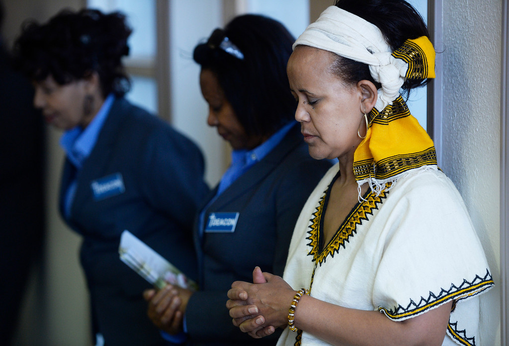 . AURORA, CO. - JANUARY 11:  Addis Kidan Evangelical Church member, Elizabeth Zewdie, right, prays during the church dedication service Saturday morning, January 10, 2014. (Photo By Andy Cross / The Denver Post)