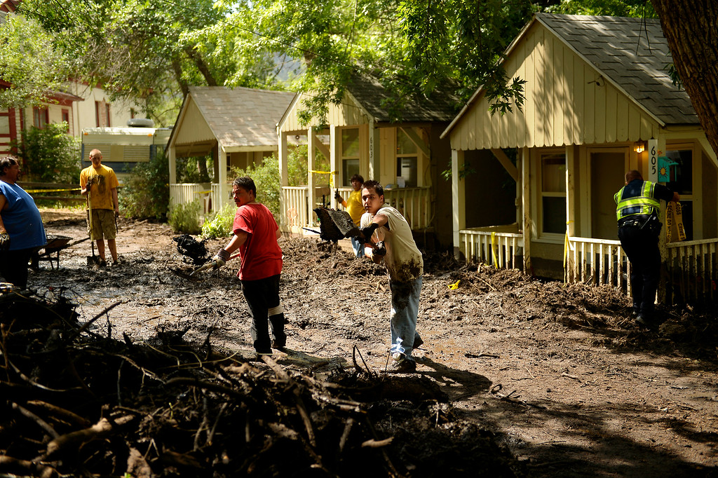 . Manitou Springs, CO. - July 02: Vincent Maloco and his son Joseph with PM Enterprises throwing mud to clear homes that took the brunt of a flash flood that washed through houses, streets and businesses when a downpour hit over the Waldo Canyon burn scar in El Paso County July 02, 2013 Manitou Springs, Colorado. (Photo By Joe Amon/The Denver Post)