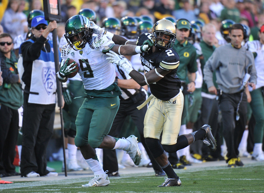 . BOULDER, CO - OCTOBER 05 : RB Byron Marshall of University of Oregon (9) controls the ball against DB Kenneth Crawley of University of Colorado (2) in the 2nd quarter at Folsom Field. Boulder, Colorado. October 5, 2013. (Photo by Hyoung Chang/The Denver Post)