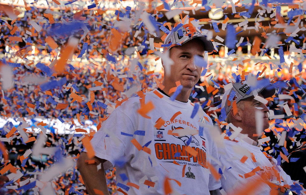 . Denver Broncos quarterback Peyton Manning (18), takes in the moment with Denver Broncos head coach John Fox, right, as the confetti flies all around them after the Broncos won the AFC Championship game.  The Denver Broncos vs. The New England Patriots in an AFC Championship game  at Sports Authority Field at Mile High in Denver on January 19, 2014. (Photo by Helen H. Richardson/The Denver Post)