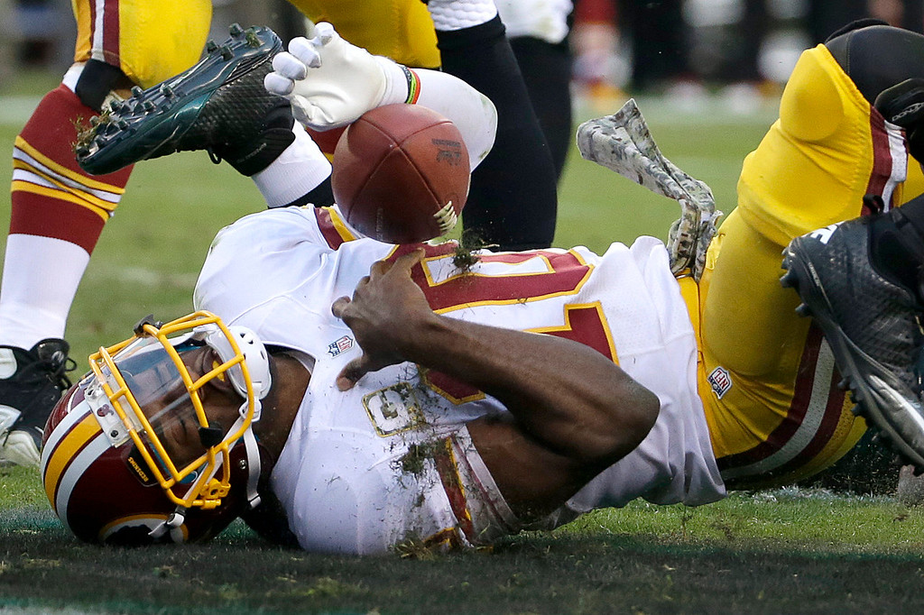 . Washington Redskins quarterback Robert Griffin III lands after rolling into the end zone for a two-point conversation during the second half of an NFL football game against the Philadelphia Eagles in Philadelphia, Sunday, Nov. 17, 2013. (AP Photo/Matt Slocum)