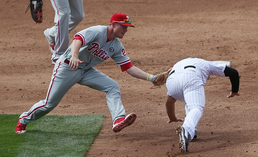 . Philadelphia Phillies third baseman Cody Asche, left, tags out Colorado Rockies\' Nolan Arenado after he was caught in a rundown between first and second base to end the third inning of a baseball game in Denver on Sunday, April 20, 2014. (AP Photo/David Zalubowski)
