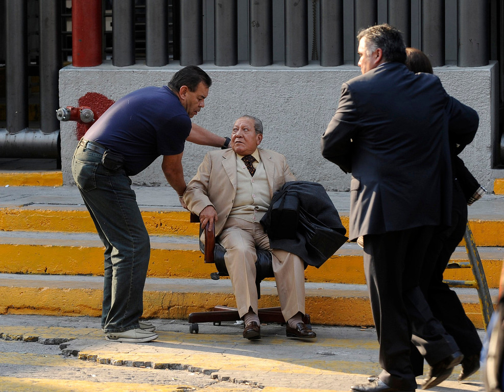 . An elderly man is being helped outside the headquarters of state oil giant Pemex in Mexico City January 31, 2013. A powerful explosion rocked the Mexico City headquarters of state oil giant Pemex on Thursday, killing at least 14 people and injuring 100 others.    REUTERS/Alejandro Dias
