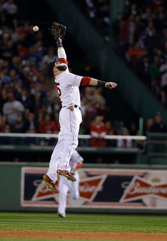 . Boston Red Sox second baseman Dustin Pedroia leaps, but can\'t field a hit by Detroit Tigers\' Omar Infante in the second inning during Game 6 of the American League baseball championship series on Saturday, Oct. 19, 2013, in Boston. (AP Photo/Matt Slocum)