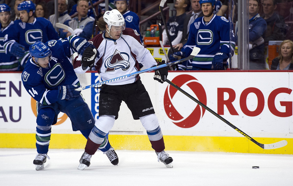 . Alexandre Burrows #14 of the Vancouver Canucks and PA Parenteau #15 of the Colorado Avalanche battle for the puck during the first period in NHL action on March 28, 2013 at Rogers Arena in Vancouver, British Columbia, Canada.  (Photo by Rich Lam/Getty Images)