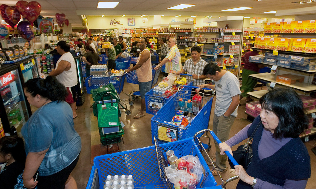 . Hundreds of Oahu residents flocked to the Times Supermarket to purchase water and supplies Thursday, March 10, 2011 in Honolulu. The state of Hawaii is under a tsunami warning due to a large 8.9 earthquake off Japan. The earthquake is believed to have generated a tsumani wave. The Pacific Tsunami Center expects the wave to hit Hawaii at 2:59 a.m. Hawaiian Standard Time. (AP Photo/Eugene Tanner)