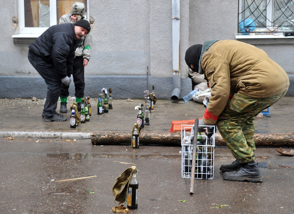 ". Pro-Russia activists prepare  Molotov cocktails as they guard a barricade outside a regional police building seized by armed separatists in Slavyansk on April 13, 2014. Ukraine on Sunday launched an ""anti-terrorist operation\"" in the eastern town of Slavyansk, where pro-Russian gunmen have seized police and security services buildings, Interior Minister Arsen Avakov said. AFP PHOTO / GENYA SAVILOV"