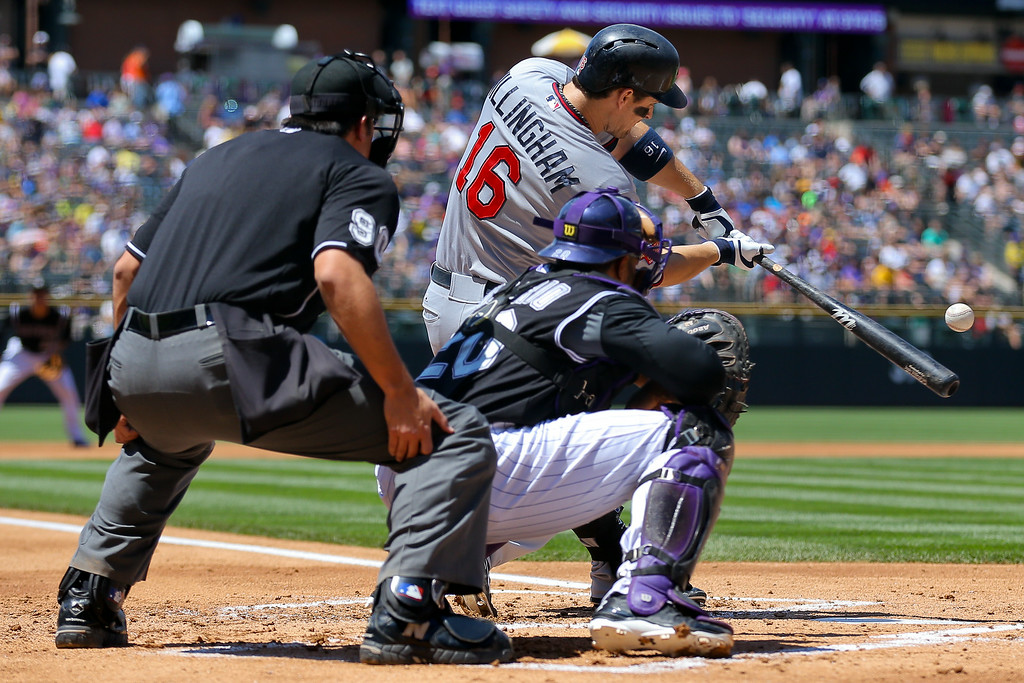 . Josh Willingham #16 of the Minnesota Twins hits a single during the first inning as catcher Wilin Rosario #20 of the Colorado Rockies and home plate umpire Mark Ripperger look on during the first inning at Coors Field on July 13, 2014 in Denver, Colorado. (Photo by Justin Edmonds/Getty Images)