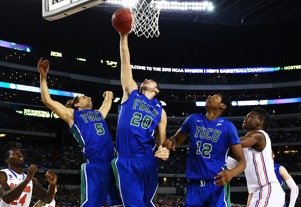 . ARLINGTON, TX - MARCH 29:  Chase Fieler #20 rebounds between Christophe Varidel #5 and Eric McKnight #12 of the Florida Gulf Coast Eagles in the first half against the Florida Gators during the South Regional Semifinal round of the 2013 NCAA Men\'s Basketball Tournament at Dallas Cowboys Stadium on March 29, 2013 in Arlington, Texas.  (Photo by Tom Pennington/Getty Images)