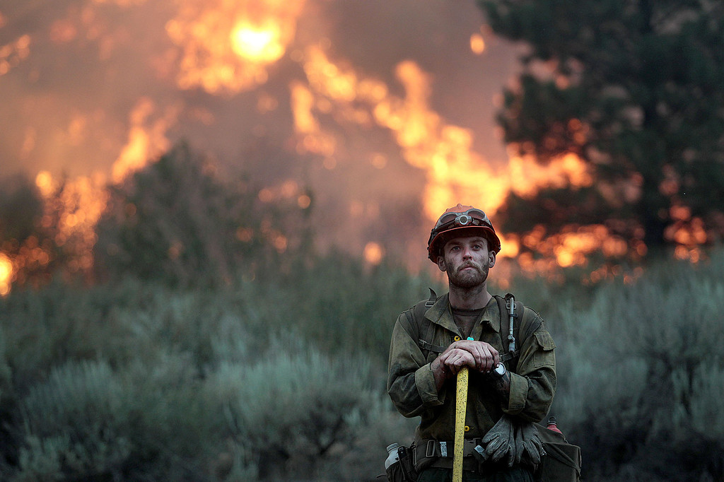 . In this Monday, Aug. 12, 2013 photo, a firefighter with the Idaho City Hotshots looks for spot fires during a back burn along the Pine-Featherville Road while battling the more than 90,000-acre Elk Fire Complex near Pine, Idaho.  (AP Photo/The Times-News, Ashley Smith)